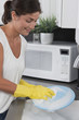 Hispanic woman washing dishes in kitchen