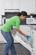 Hispanic woman putting bowl in dishwasher