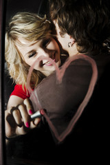 Woman drawing heart with lipstick on mirror while hugging boyfriend