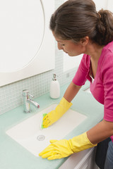 Hispanic woman cleaning bathroom sink