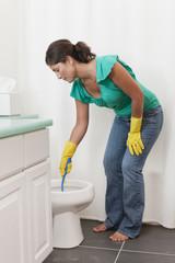 Hispanic woman scrubbing toilet in bathroom
