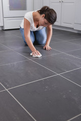 Hispanic woman cleaning kitchen floor