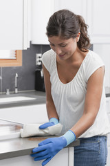 Hispanic woman cleaning kitchen counter