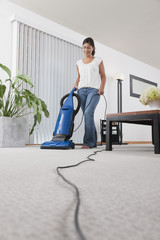 Hispanic woman vacuuming living room floor