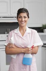 Hispanic maid cleaning kitchen