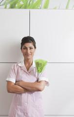 Hispanic maid dusting cabinet