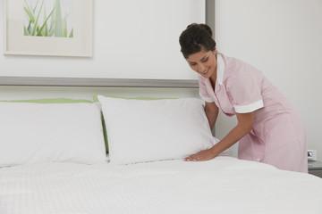 Hispanic maid making bed