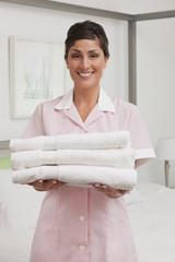 Hispanic maid carrying folded towels