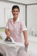 Hispanic maid ironing shirt
