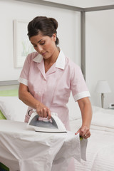 Hispanic maid ironing shirt