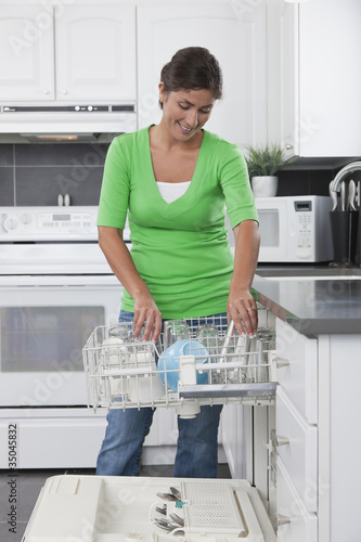 Hispanic woman unloading dishwasher