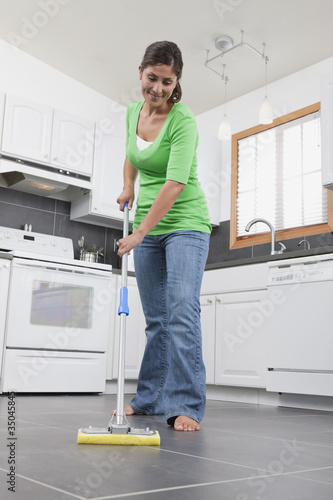 Hispanic woman mopping kitchen floor