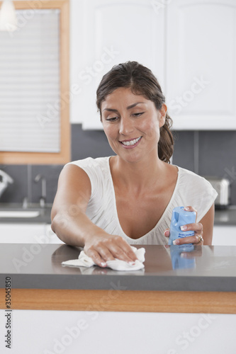 Hispanic woman dusting counter