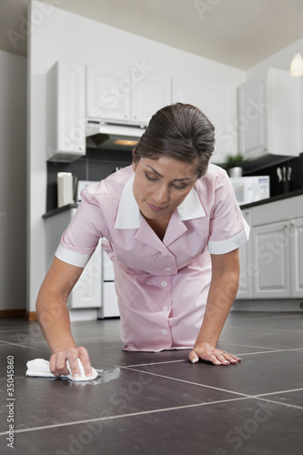 Hispanic maid cleaning kitchen floor