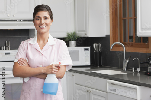Hispanic maid cleaning kitchen