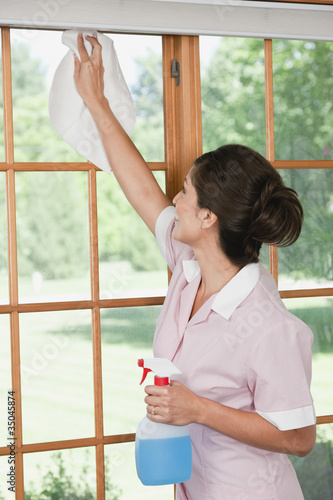Hispanic maid cleaning windows