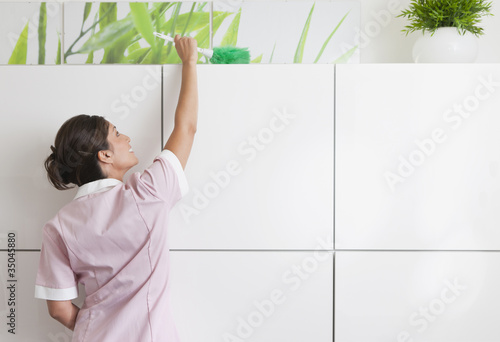 Hispanic maid dusting cabinet