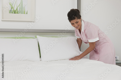 Hispanic maid making bed