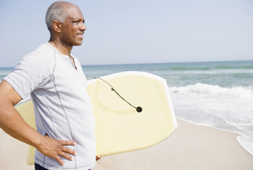Black man holding body board on beach