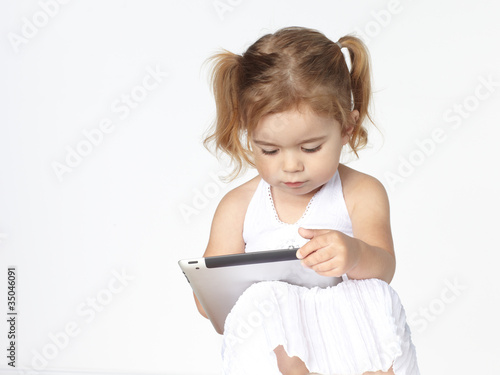 Cute little girl  is playing concentrated with touchpad