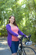 Pregnant Caucasian woman standing with bicycle