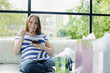 Pregnant Caucasian woman eating on sofa at baby shower