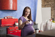 Pregnant Caucasian woman text messaging in kitchen
