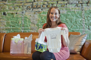 Pregnant Caucasian woman opening baby shower gifts