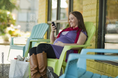 Pregnant Caucasian woman text messaging outdoors