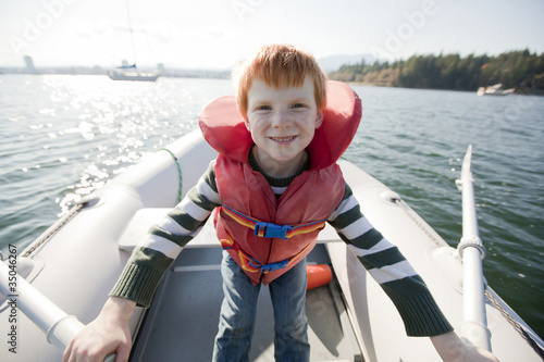 Caucasian boy rowing on boat