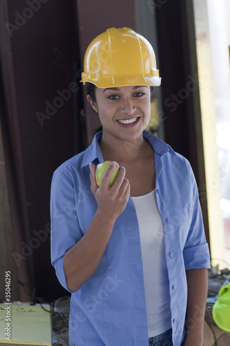 Hispanic sanitation worker eating an apple