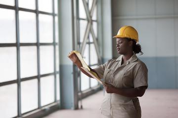 Black worker in hard-hat looking at clipboard