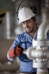 Hispanic worker turning valve on pipe