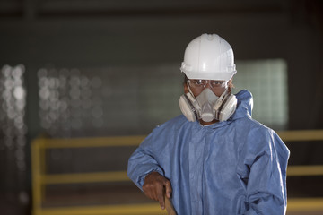 """Black worker in hazmat suit, hard-hat and face mask"""