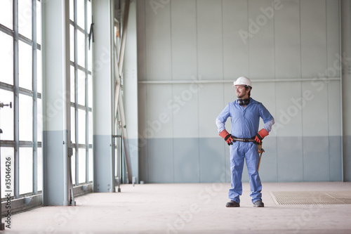 Hispanic worker in hard-hat standing indoors