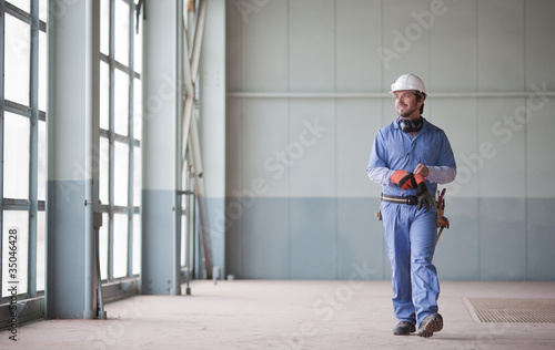 Hispanic worker in hard-hat walking indoors