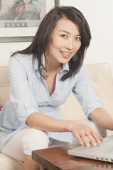 Korean woman using laptop in living room