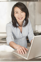 Korean woman using laptop in kitchen