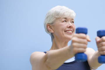 Mixed race woman exercising with dumbbells