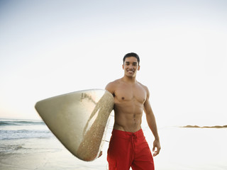 Mixed race man carrying surfboard on beach