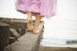 Mixed race girl in costume walking on dilapidated pier