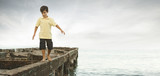 Mixed race boy walking on dilapidated pier