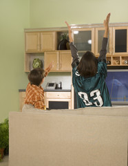 Mother and son cheering at football game on television