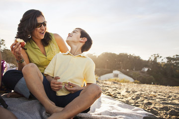 Mother and son enjoying picnic on beach