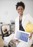 Black businesswoman holding solar panel