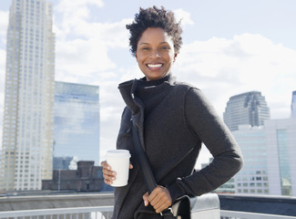 Black woman drinking coffee on rooftop