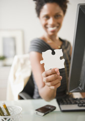 Black businesswoman holding puzzle piece at desk