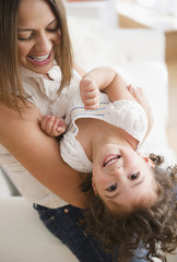 Mother lifting laughing daughter