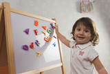 Hispanic baby playing with letters on magnetic board