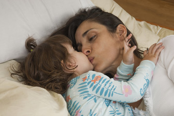 Hispanic mother kissing daughter in bed